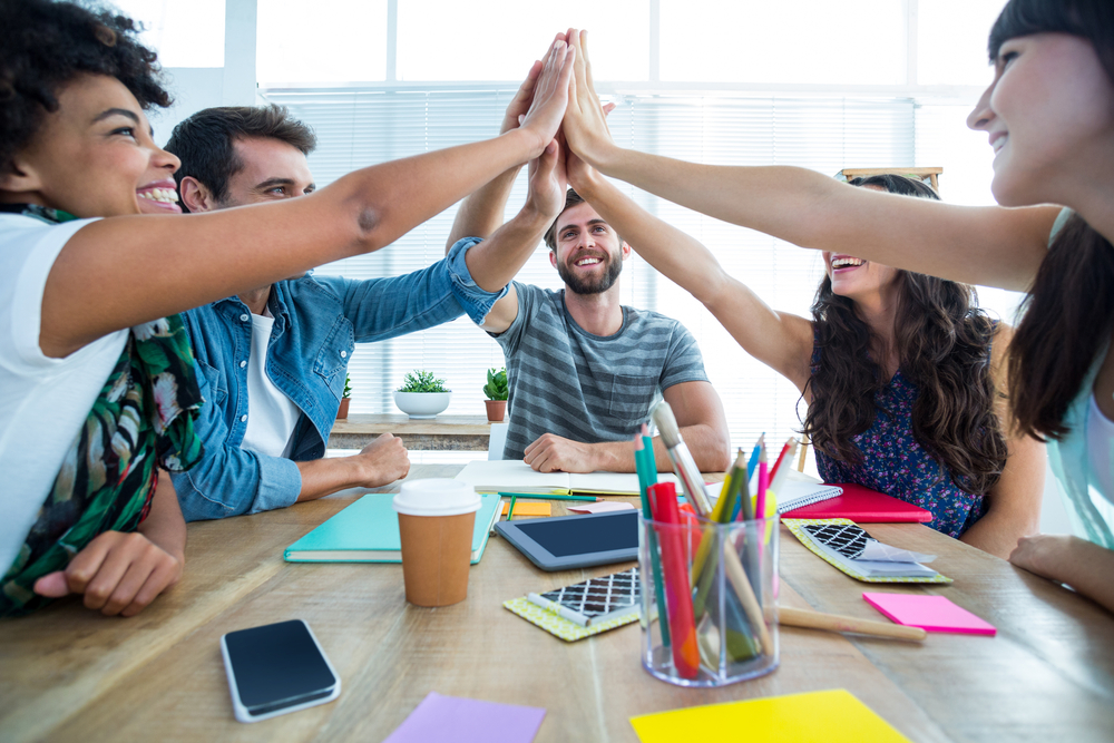 You won't have to take one for the team. Creative business team putting hands together as a success high five at the office over meeting table