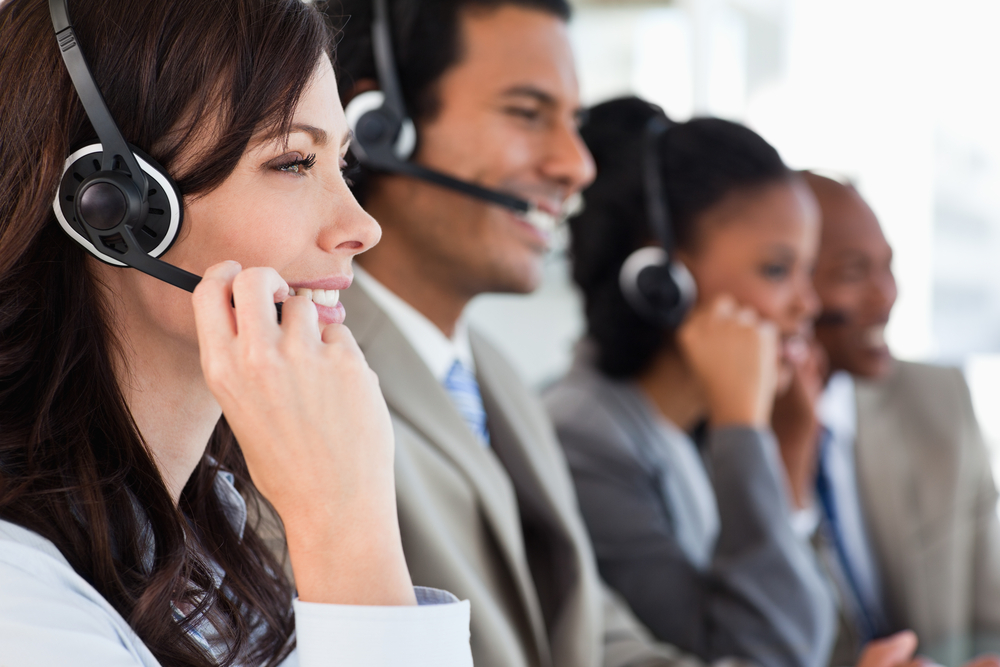 what are the main needs of a customer. Young employee listening to headset interested in customer needs, accompanied by her team