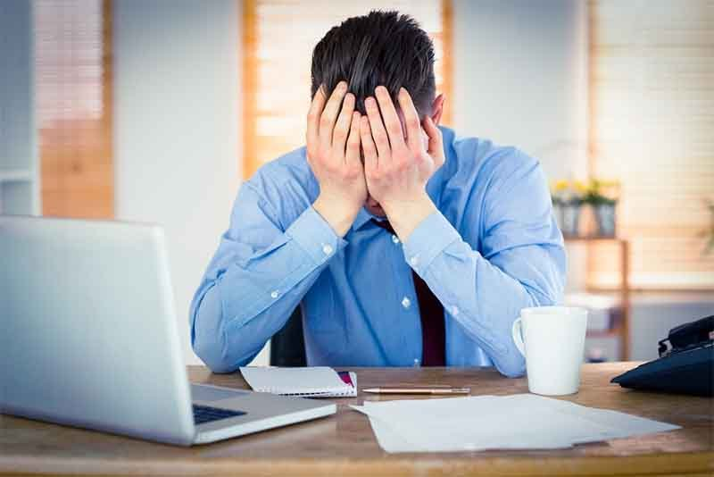 Stressed businessman with head in hands at office, website not performing, traditional website methods